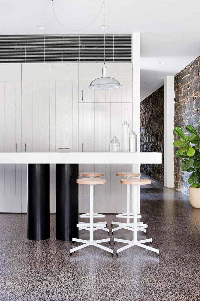 """Modern elements, such as the white and timber [bar stools](https://www.homestolove.com.au/how-to-buy-the-perfect-bar-stool-22680 target=""""_blank"""") enhance the rough texture of exposed bluestone walls. There is a certain feeling of peace given by stone, timber and all things sourced form the earth."""