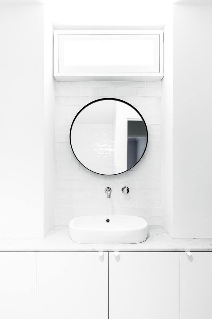 "This white-on-white bathroom in a [minimalist Sydney apartment](https://www.homestolove.com.au/minimalist-makeover-a-sydney-apartment-gets-a-fresh-start-16703|target=""_blank"") features a light above the vanity that looks like a window, ""It gives this soft glow and makes you feel better that it's there,"" says the homeowner."