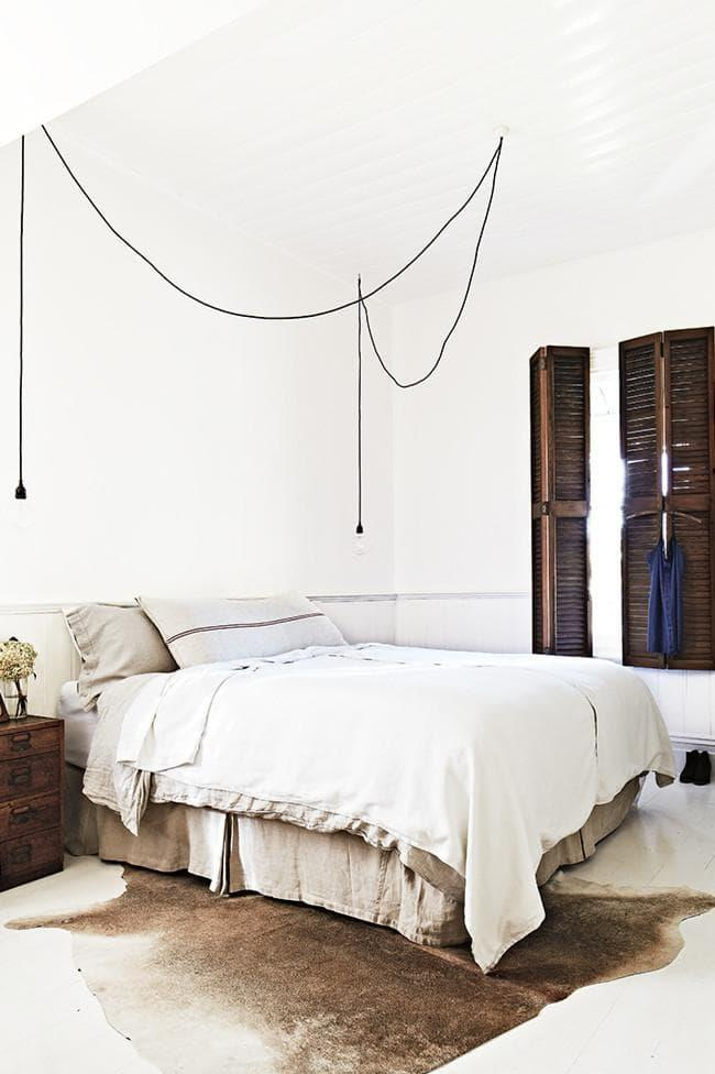 Raw linen and wood louvred doors give this white bedroom a relaxed and natural appeal. With a canvas comprising of dramatically white floors, panelled ceilings and walls, the tonal bedlinen and hide rug add a striking contrast.