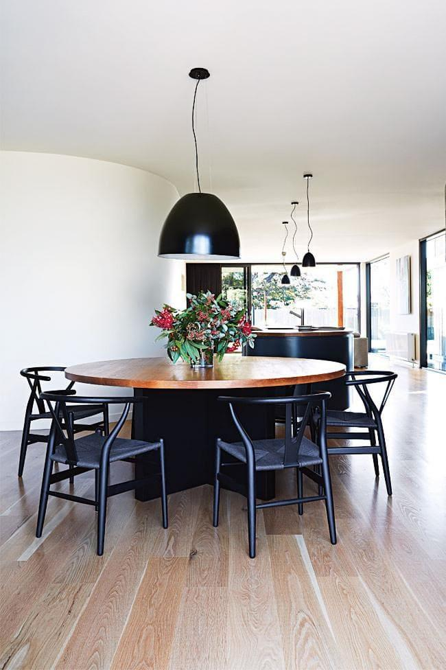 **Black chairs and large pendant lights provide a striking contrast to the light wood floors** Photographer: Armelle Habib