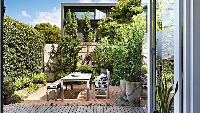 Plants and vines placed strategically around the edges of this garden help to soften the paved back area. *Photo: Armelle Habib*   *Styling:* Julia Green