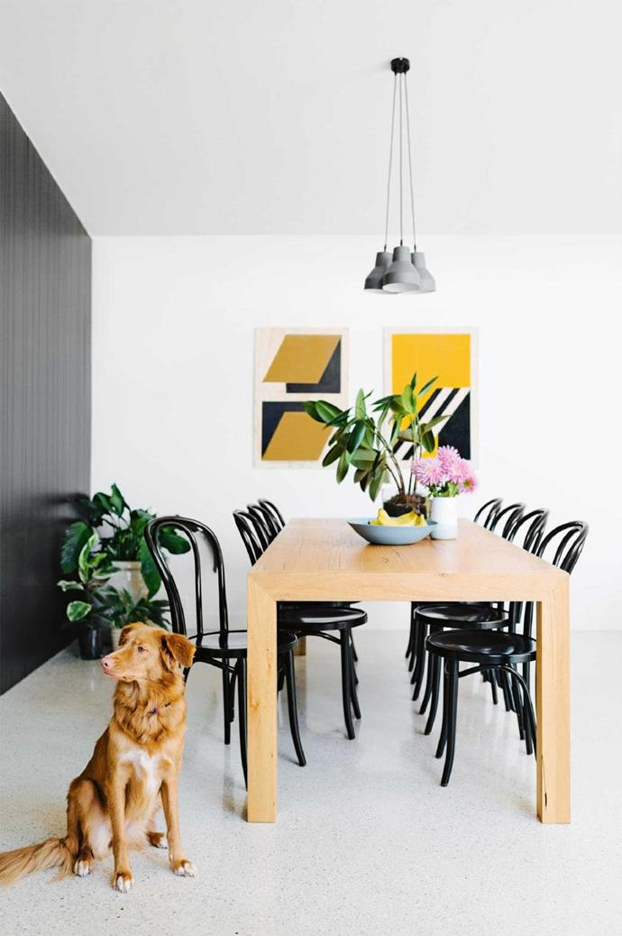 Bold geometric artworks by Marcus Hollands elevate the tones of the timeless dining setting. A cluster of Mud Australia porcelain lights mirror the home's modern elegance Photographer: Brooke Holm, Stylist: Marsha Golemac