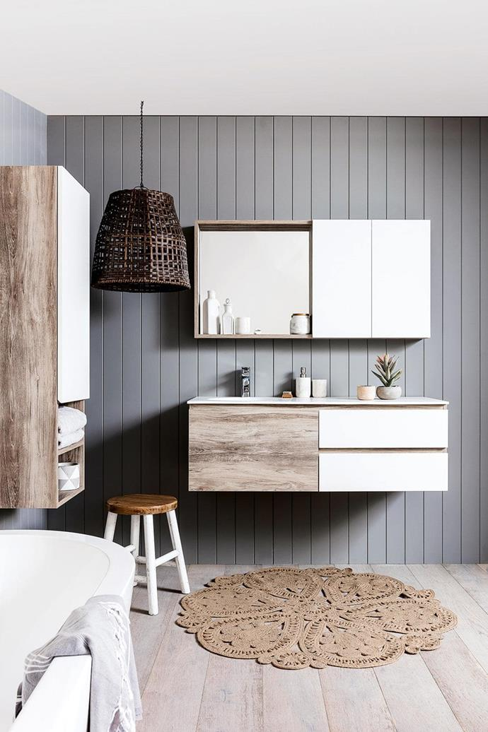 "A [coastal boho vibe](https://www.homestolove.com.au/beach-boho-this-coastal-home-nails-white-on-white-design-7048|target=""_blank"") has been channeled in this bathroom with panelled walls, sisal rug and distressed timber cabinetry. *Photo: Armelle Habib / Styling: Julia Green*"