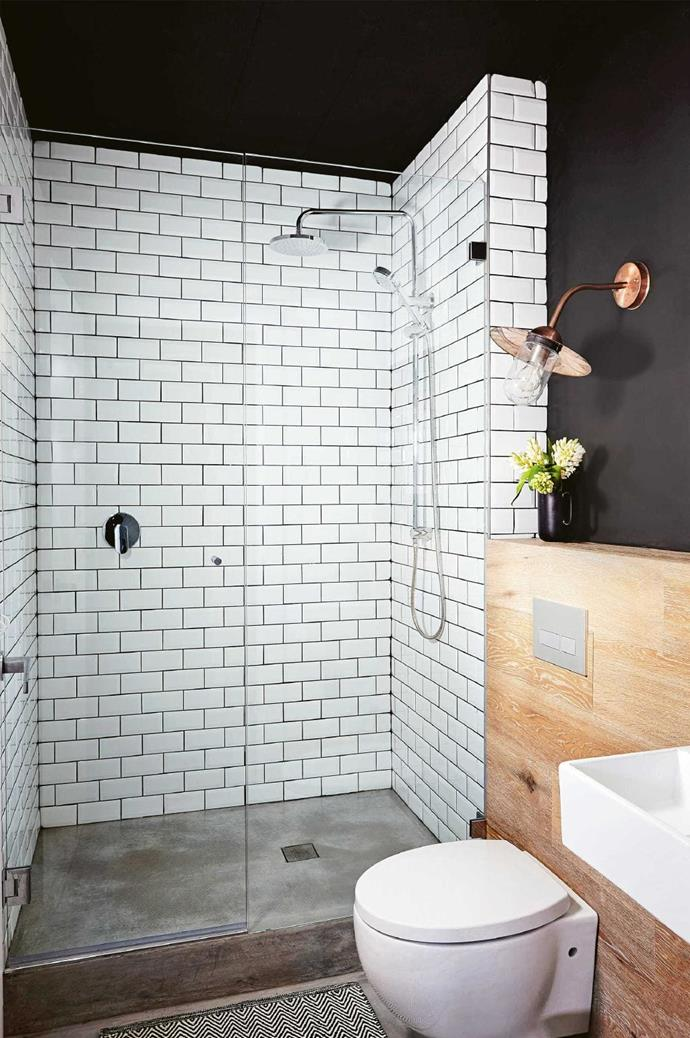 The combination of white subway tiles, black wall, concrete floor and timber accent gives this bathroom a rich sense of texture