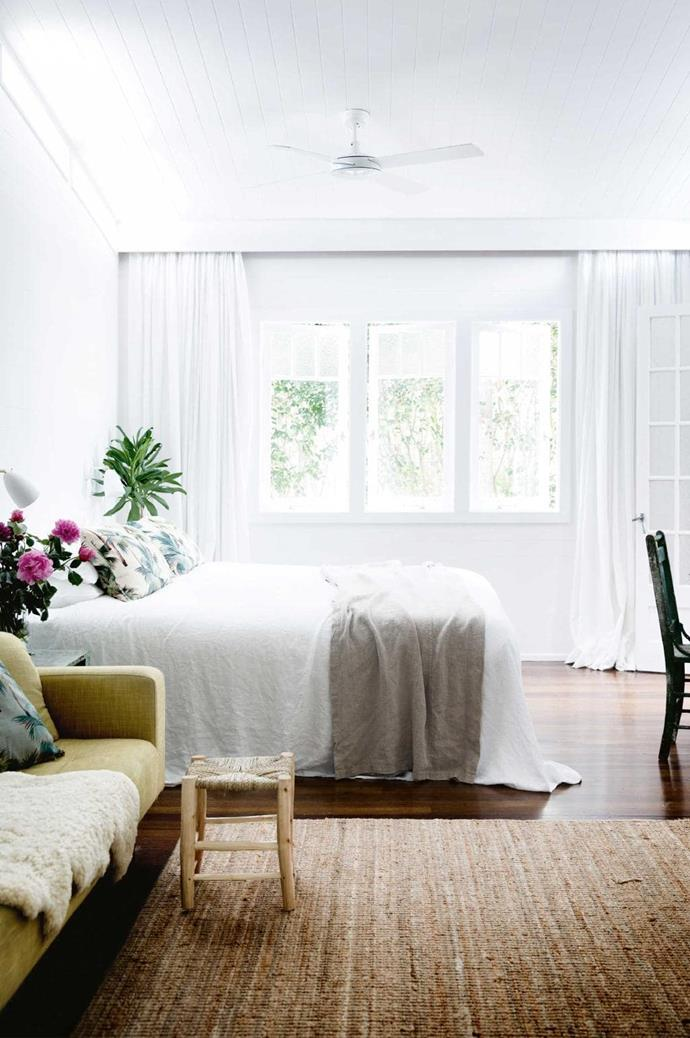Lightweight curtains, tactile neutral coloured accessories and a hint of greenery create a casual and calm sleep haven. Despite the darker flooring and the jute rug, the soft white curtains and white bedlinen impart a sense of calmness to the space.
