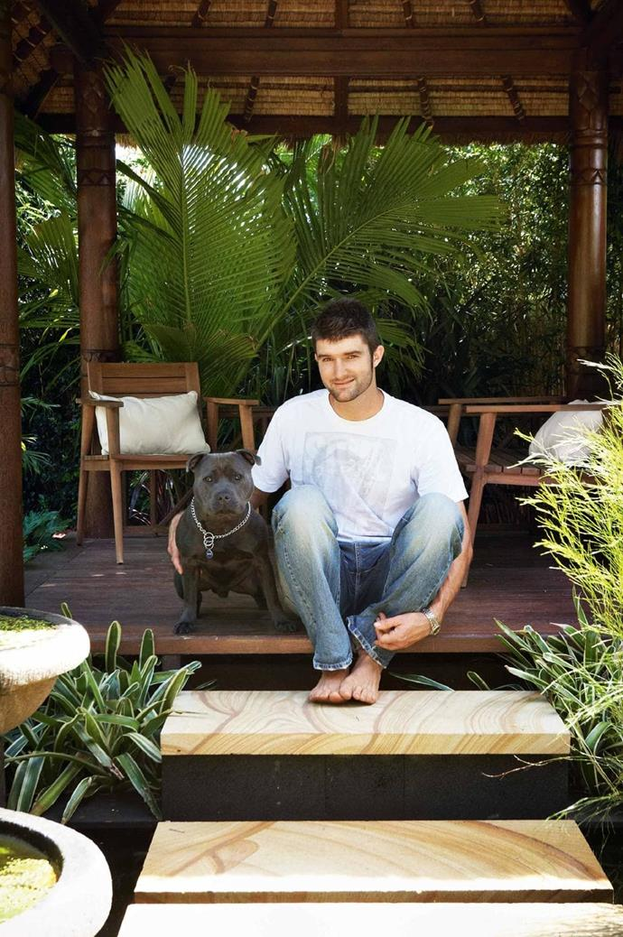 """With his dog, Austin, Clint sits in the Bali hut located by the koi carp pond. """"The thatch roof  <br />is surprisingly cool in the hot sun,"""" he says Photographer: Michael Wee, Stylist: Phoebe McEvoy"""