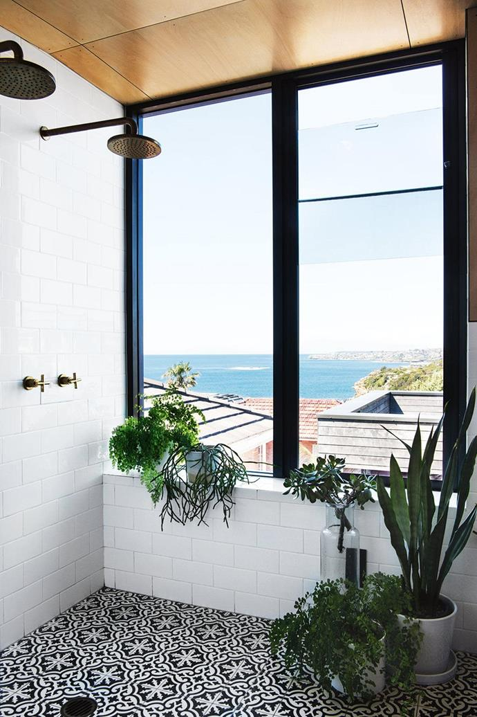 "Huge windows frame the ocean views visible in this bathroom in a [newly built modern home](https://www.homestolove.com.au/a-new-build-that-combines-modern-design-with-bright-colour-15874|target=""_blank"") while a group of indoor plants enliven the space. *Photo: Armelle Habib / Stylist: Julia Green*"