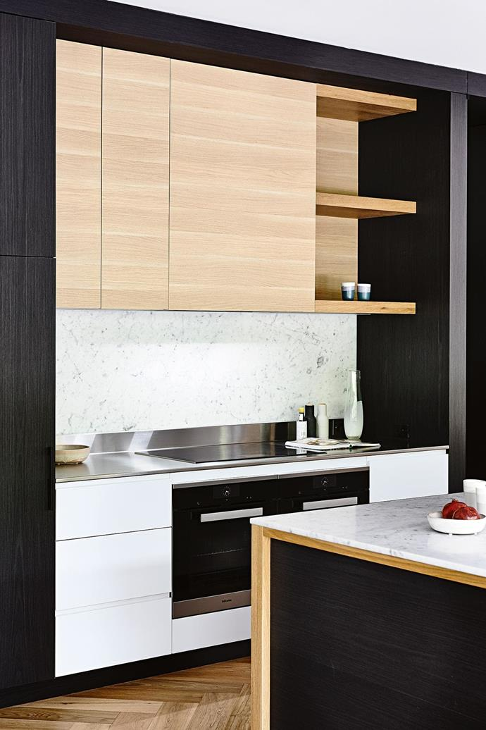 "**MIXED MATERIALS** <br><br>Free yourself from the idea that cabinetry and benchtops must all match, and you might find yourself with a more inspiring palette. In this kitchen, luxe marble on the [island bench](https://www.homestolove.com.au/kitchen-inspiration-13-of-the-best-island-benches-17943|target=""_blank"") complements practical stainless steel on the workbench. Meanwhile, black timber veneer frames white cabinets below and oak cupboards with open shelving above.<br><br>"