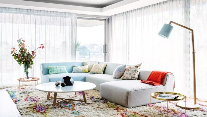 A fairy godmother in the form of an interior designer helped this Perth family get through a challenging renovation. A pastel palette perfectly complements the light-filled and airy living area. A shaggy rug adds texture and pulls the look of the room together. Photographer: Brooke Holm | Stylist: Sophie Thé