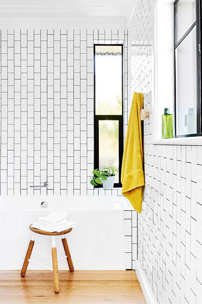 """AFTER """"The biggest bargain in the room has got to be my bathtub. It's a simple Bunnings buy that looks and fits in perfectly with the space,"""" says Lena. Uncovering pristine Tasmanian oak floorboards was one of the greatest discoveries of the renovation process. """"We limed them, but I just couldn't bring myself to mess too much with the colour – they're just so beautiful"""" Photographer: Brooke Holm, Stylist: Marsha Golemac"""