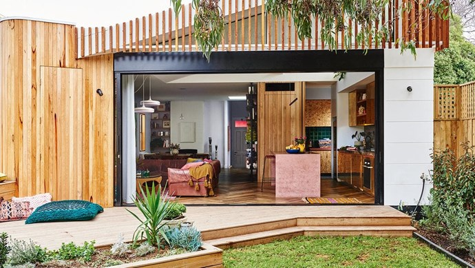 """Sliding doors open up the kitchen and living areas to the outside. """"You feel like you've doubled your living space,"""" says homeowner Alex. Blackbutt timber was used for the deck and American oak for the cladding. Photography by Nikole Ramsay. Photographer: Nikole Ramsay"""
