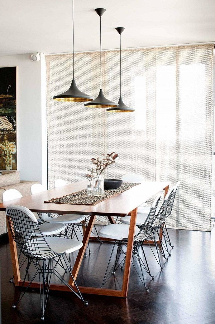 This modern and sophisticated dining area features Tom Dixon 'Beat' pendant lights, 'Fineline' dining table and 'Eiffel' chairs from Spence & Lyda. Sunlight through the huge windows is screened by Missoni Home 'Jalpa' fabric Photographer: Sam McAdam-Cooper