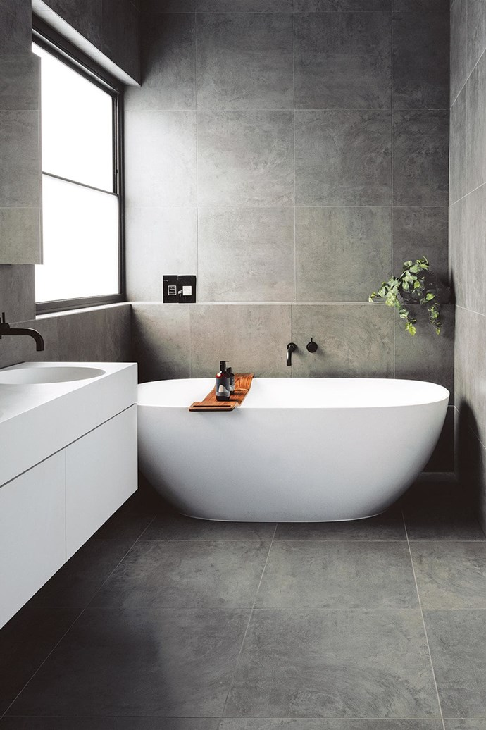 Flooded with natural light, this bathroom's choice of large cement-look tiles gives the space a cocooning feeling.