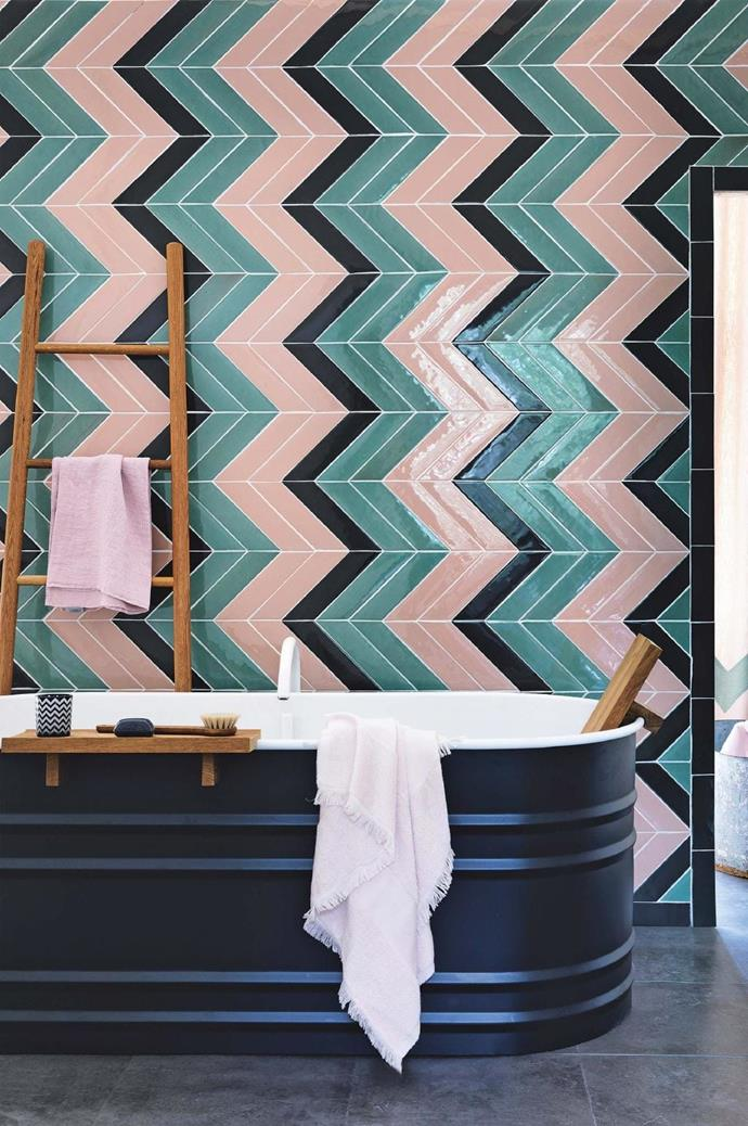 The utilitarian quality of a steel bath by Patricia Urquiola is a fitting foil to an eye-catching multi-toned chevron pattern. Timber elements seen in the bath accessories and a ladder add a natural finishing touch that complements the various tones throughout Photographer: Simon Brown/timeincukcontent.com, Stylist: Leesa O'Reilly