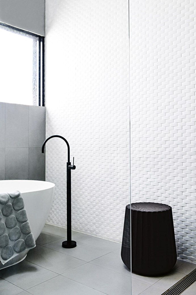 """A floor-to-ceiling wall of white basket-weave tiles takes this [luxurious modern bathroom](https://www.homestolove.com.au/luxury-modern-bathrooms-4329