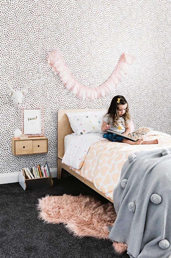 Willow's room: Willow gets a feature wall of her own, decked in 'Scallop Dots' wallpaper from [These Walls](https://thesewalls.com.au/). The bed and wall-hung storage are both from local company, [Plyroom](https://www.plyroom.com.au/). The bed is decked in vivid [Castle](https://www.castleandthings.com.au/) bedlinen and topped off by a plush pompom blanket from [Kip&Co](https://kipandco.com.au/) Stylist: Kerrie-Ann Jones, Photographer: Maree Homer