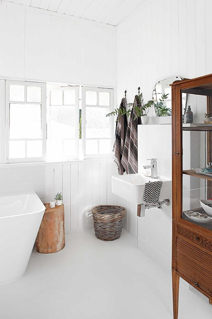 To create a sense of warmth, timber furniture pieces and earthy coloured accessories have been introduced into this all-white bathroom. *Photo: Anastasia Kariofyllidis / Styling: Simone Barter*