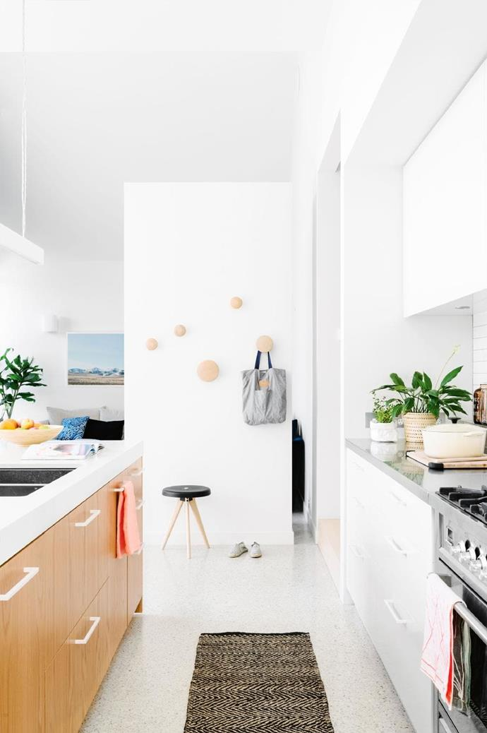 Polished aggregate floors and the Caesarstone-topped island complement the clean tones throughout the house. Muuto 'The Dots' timber wall hooks and oak cabinetry add warmth to the cool space Photographer: Brooke Holm, Stylist: Marsha Golemac