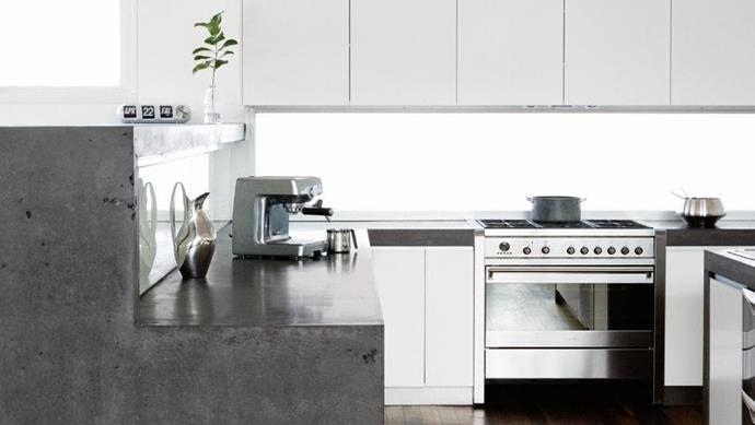 White handle-less cupboards, polished concrete bench tops and stainless steel accessories provide a sleek utilitarian style kitchen Photographer: Sam McAdam-Cooper, Stylist: Vanessa Colyer Tay