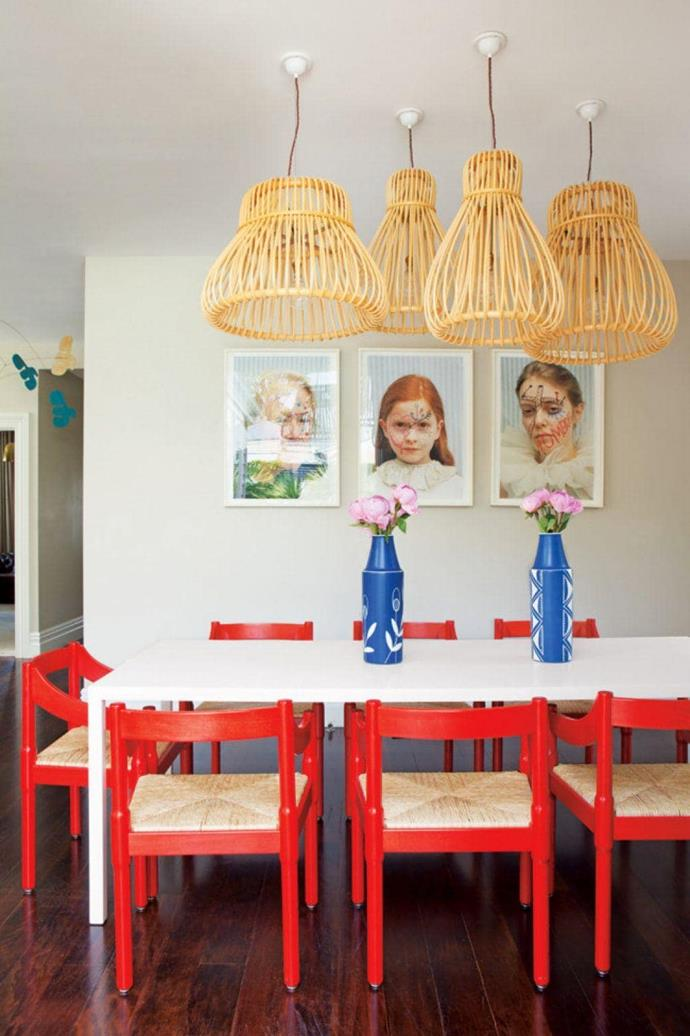 Rattan lights by [Vittorio Bonacina](http://www.bonacinavittorio.it/) are juxtaposed with red chairs by Vico Magistretti creating a relaxed beach vibe enhanced by the natural light filtering through Photographer: Emma Bass