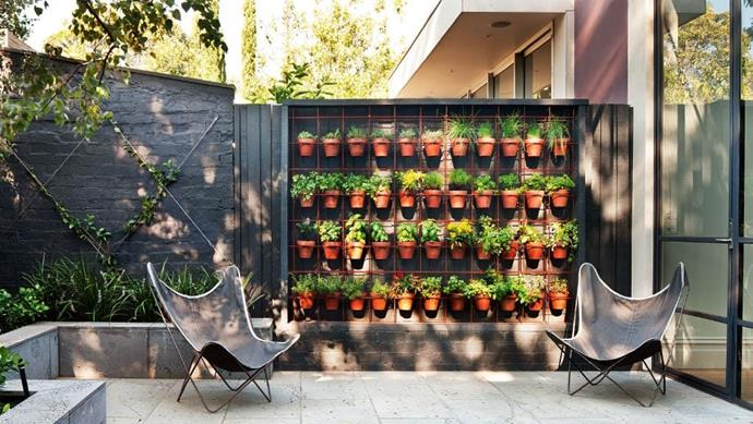 """The horizontal and vertical rods are welded and drilled into the frame to support the collected weight of the terracotta pots filled with herbs in this stacked herb [vertical garden](https://www.homestolove.com.au/vertical-garden-design-16605