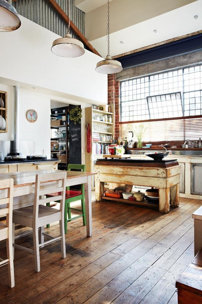 Natural light fills the industrial-style kitchen. A stripped timber island and pendant lamps with visible wear and tear add to the time-worn look Photographer: Armelle Habib