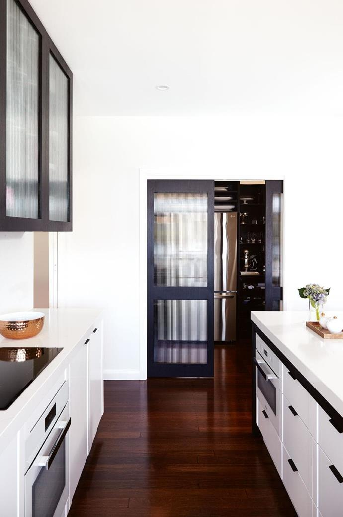 In this kitchen by [Horton & Co.](http://hortonandco.com.au), a butler's pantry has been positioned to the side and cleverly concealed by a glass sliding door making it easy to hide dirty dishes and food prep while entertaining.