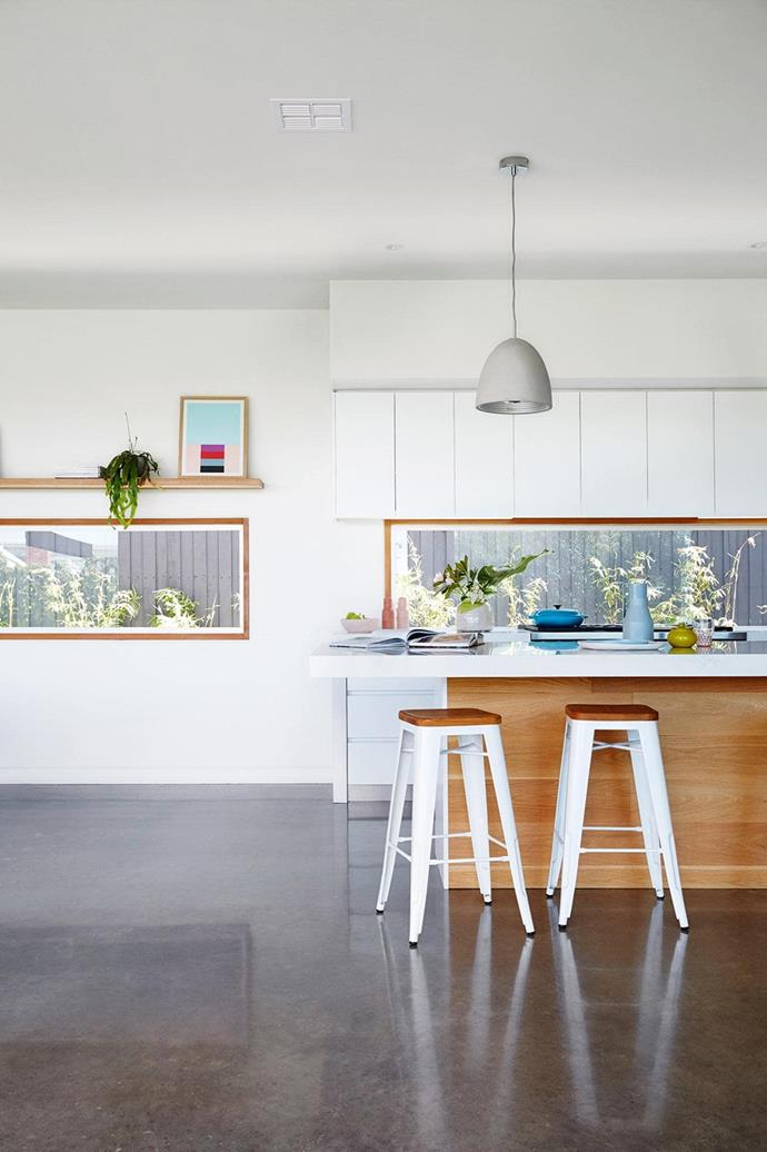"For the owners of this [newly built beach house](https://www.homestolove.com.au/a-new-build-that-combines-modern-design-with-bright-colour-15874|target=""_blank""), the window splashback in the kitchen allows them to keep an eye on their kids while they play in the yard. *Photo: Armelle Habib*"