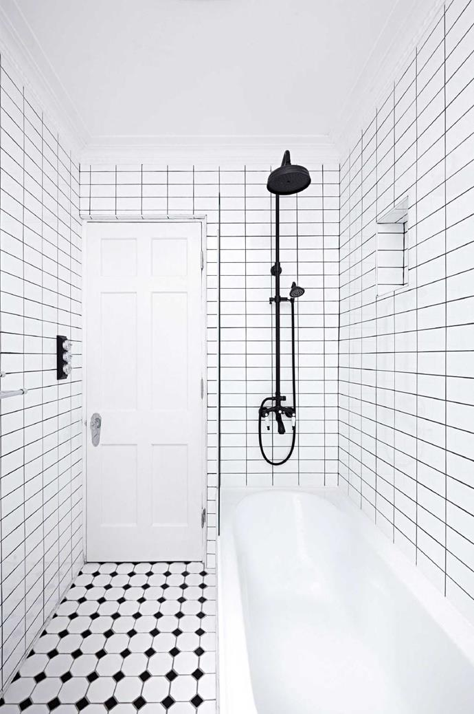 Heavier doses of black from the striking shower head, light switch and floor tiles give the bathroom a dynamic edge Photographer: Alan Richardson