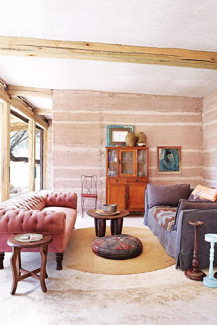 """**Living area** Darryl's pink Chesterfield sofa was inherited from a friend in Durban, while the dark-grey sofa was custom-made and Darryl's uncle made the distinctive floor lamp. [Read the full story here](https://www.homestolove.com.au/building-a-sustainable-rammed-earth-home-in-botswana-15548