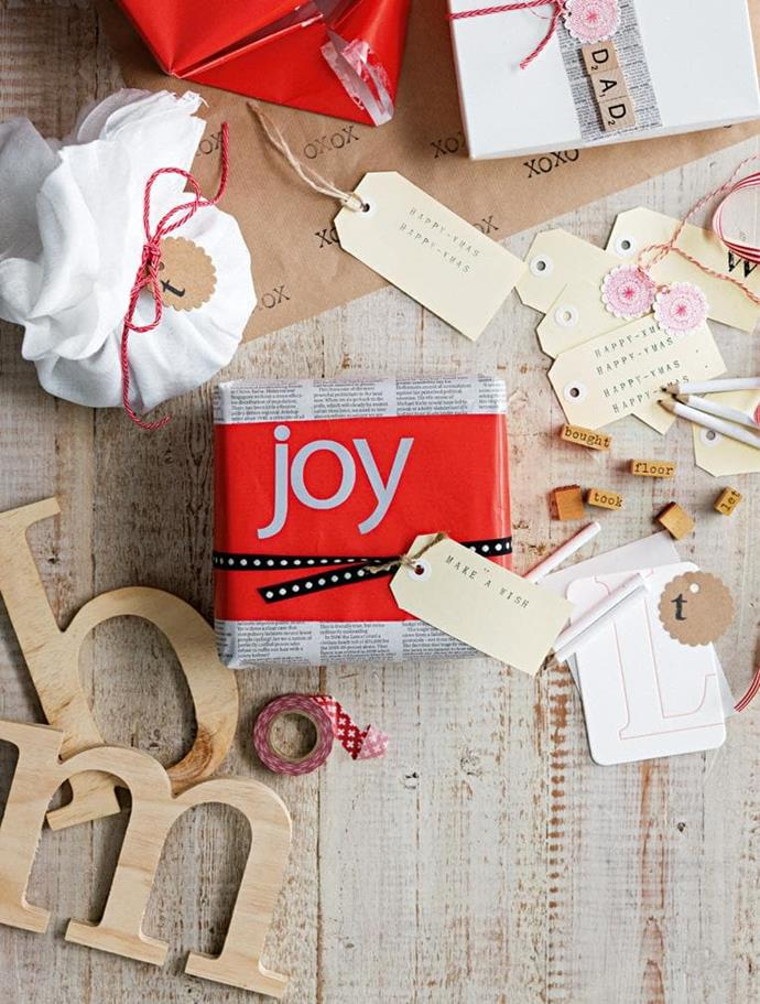 Using pages of text from magazines teamed with contrasting paper, letter stickers, cute ribbon and a hand-stamped shipping tag can make for affordable and striking gift wrap Photographer: Sam McAdam-Cooper, Stylist: Lara Hutton