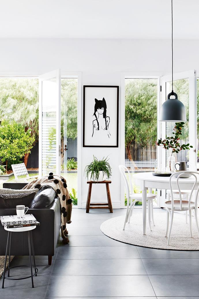 **Living and dining area** French doors with full-length windows invite the outside in, flooding the extension with natural light. A black Freedom sofa is draped with a pompom throw from Rigby's Homewares in Barwon Heads. Scroll through for the grand tour and [read the full story here](http://www.insideout.com.au/renovations/house/this-californian-bungalow-in-victoria-was-lovingly-refreshed/news-story/1ff80a7759649bff4db54980b65d85ce). Artwork: Emma Cleine, [Lumiere Art + Co](https://lumiereartandco.com.au/). _Styling by Julia Green with assistance by Georgie Fitzgerald and Emily Evans. Photography by Annette O'Brien_.