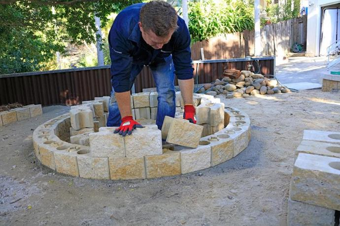 **Step 4: Laying the second course** <br> Stack the next course of blocks, making adjustments as necessary. Once installed, remove sod/vegetation from the centre of the fire pit area. Lay approximately 6 x 23 kg bags of clean rock within the circle to cover the bottom of the fire pit. Then using a shovel, rake smooth.
