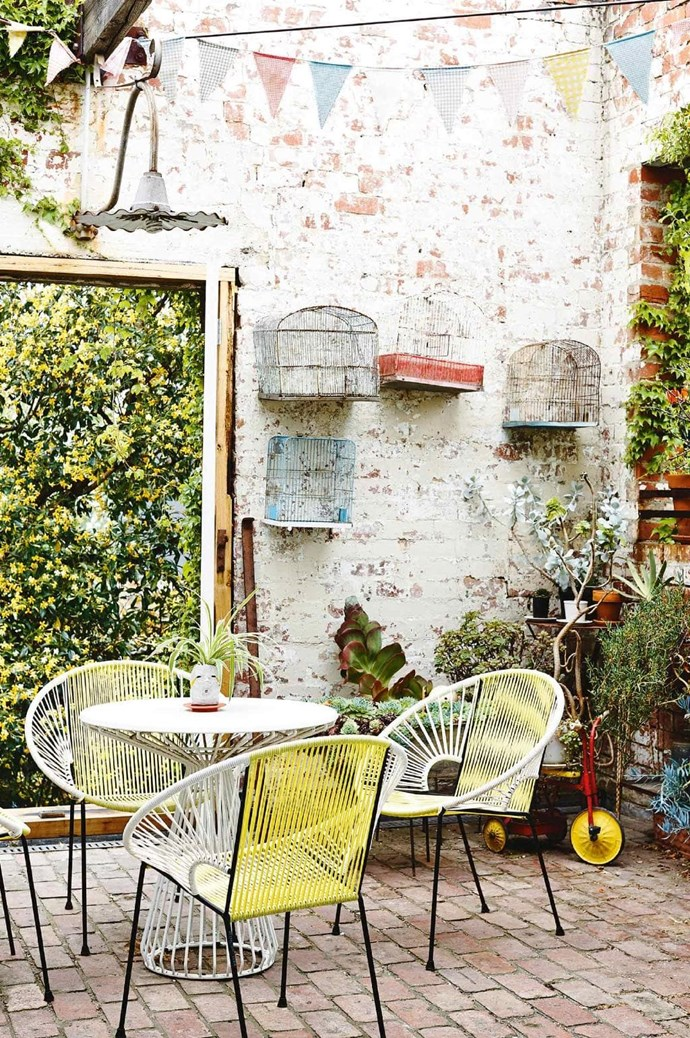 """Retro-inspired outdoor furniture, a touch of colour and a [potted plants](https://www.homestolove.com.au/top-performing-potted-plants-for-your-garden-2183 target=""""_blank"""") turn this small sunny courtyard into a functional space. *Photo:* Derek Swalwell   *Styling:* Heather Nette King,"""