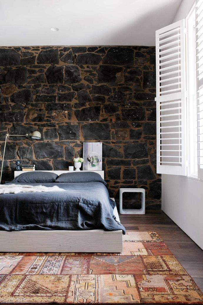 """A mix of austere and intimate pieces creates balance in the bedroom. A hardwood bed introduces tactile beauty, while the original [bluestone walls](https://www.homestolove.com.au/bluestone-farmhouse-20392 target=""""_blank"""") maintain the old soul."""