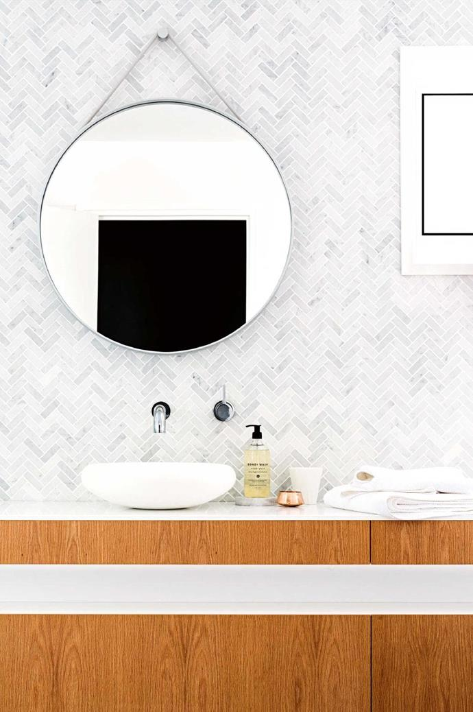Chevron marble mosaics from Surface Gallery are a simple, yet elegant feature. A circular mirror and wall-mounted mixer complete this sophisticated space Photographer: Brooke Holm, Stylist: Marsha Golemac