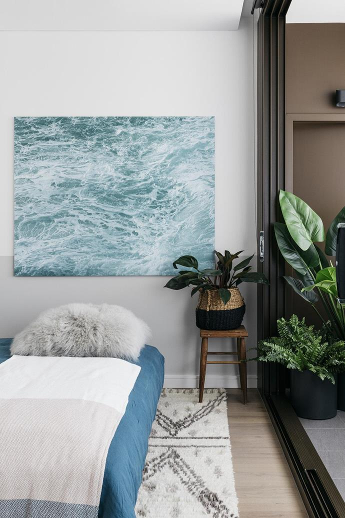 """The second bedroom has a serene vibe with a patterned berber rug, timber bedhead and ocean based artworks,&quot; says Shannon.  <i>Photography by Felix Forest</i>."