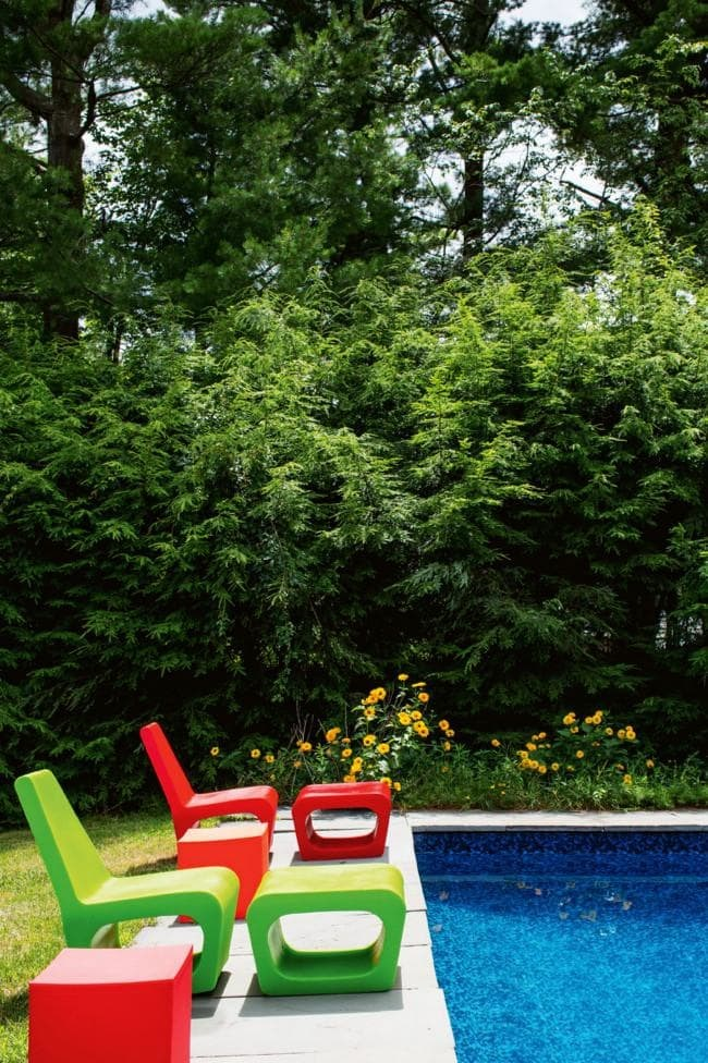 """Outside influence The zippy interior palette of this home is repeated outdoors with ultra-bright 'JellyNish' seating by Quinze & Milan. """"I love how the bold colours of the furniture stand out against the earthy tones of the pool's natural surroundings,"""" says the homeowner.  **Tip:** When using strong palettes, choose furniture with simple forms to prevent the combination being too """"loud"""" Photographer: Trevor Tondro/Living Inside"""