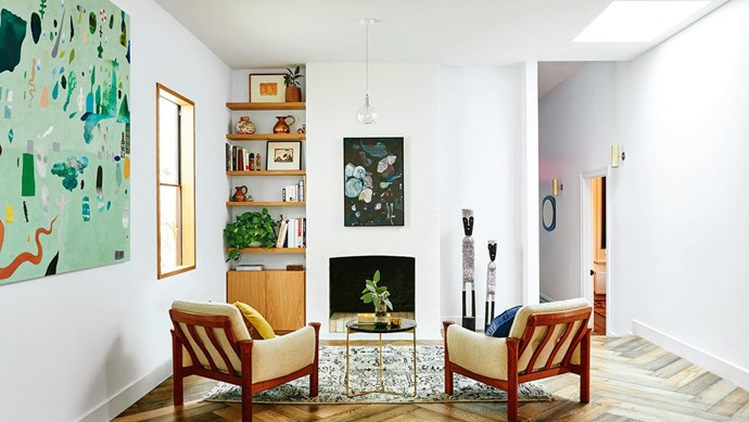 """Most of the furniture in the house is vintage – these 1950s armchairs are from [Grandfather's Axe](https://grandfathersaxe.com.au/). The statues beside the fireplace are from Elcho Island near Arnhem Land. """"My sister lived there for a long time and gave them to me for my 30th birthday,"""" says Alex. Photography by Nikole Ramsay. Photographer: Nikole Ramsay"""