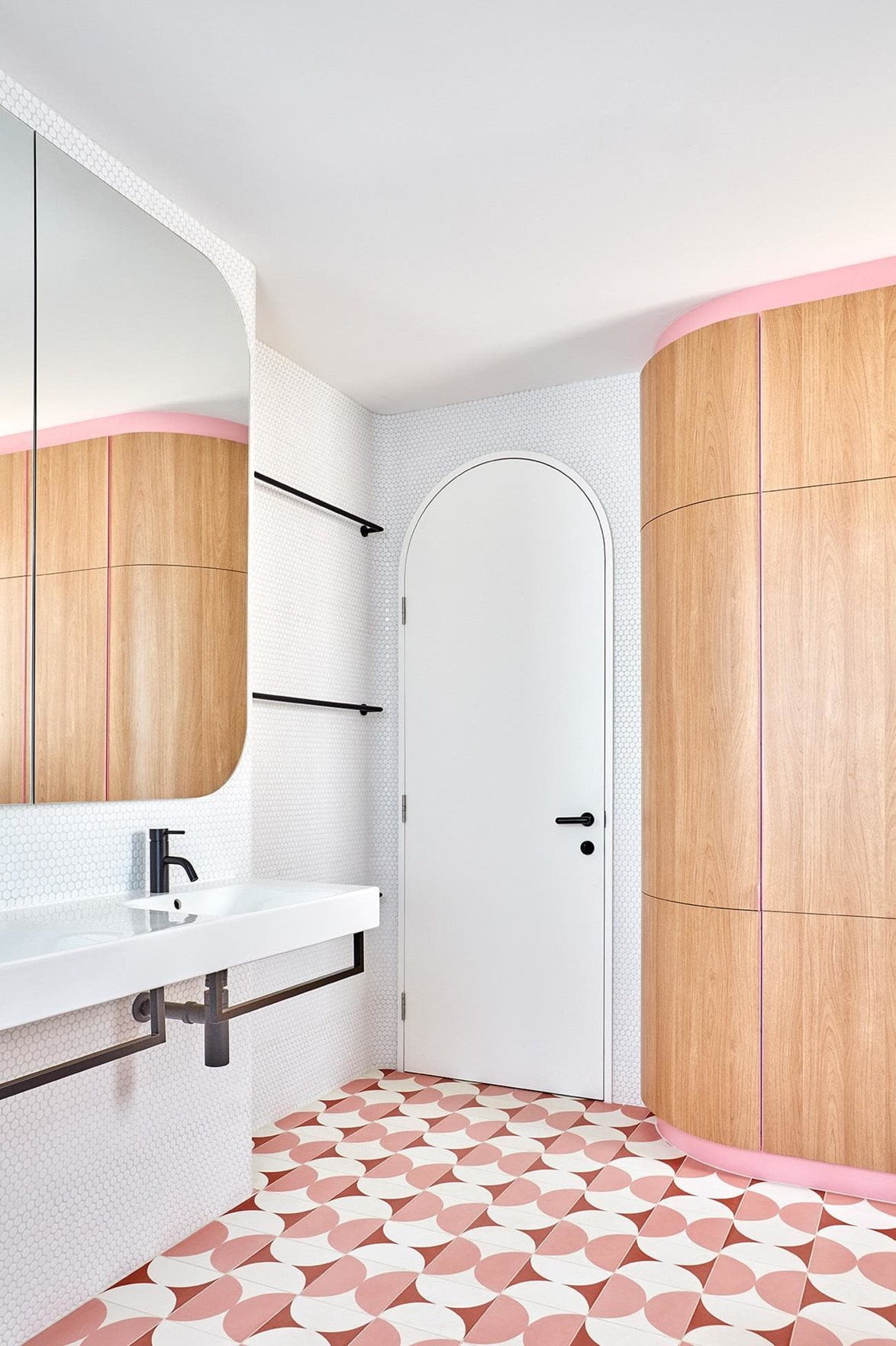 """The bathroom in this [renovated 19th century terrace](https://www.homestolove.com.au/this-renovated-19th-century-terrace-now-has-pastel-pink-floors-and-secret-doors-17195 target=""""_blank"""") features a fresh white canvas embellished with pastel pink, hand-painted encaustic floor tiles and powder pink detailing within the timber cabinetry, giving it a fresh, playful and modern feel. *Project* by Winwood McKenzie   *Photo:* Sean Fennessy"""