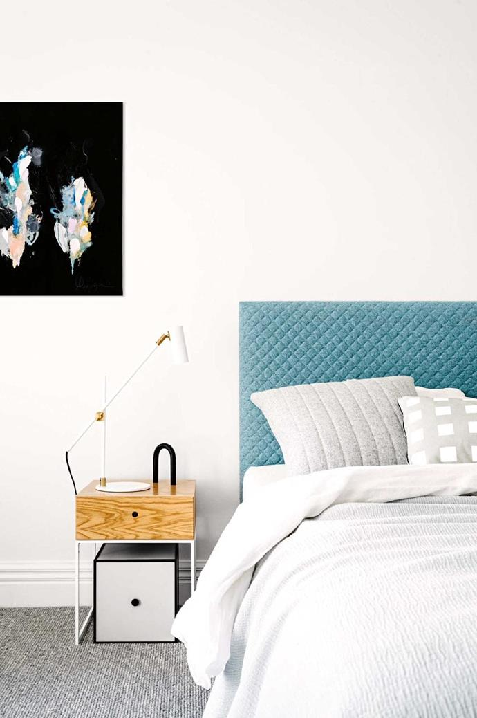 While the bedding, walls, and flooring adhere to a classic neutral palette, a statement upholstered blue bedhead and bold artwork break it up for a dramatic look.