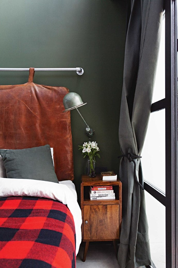 A plaid wool blanket, dark green wall and charcoal curtains gives this zone a cosy warmth. The bedhead is actually a vintage gym cushion James found in England Stylist: Marc Heldens, Photographer: Alan Jensen