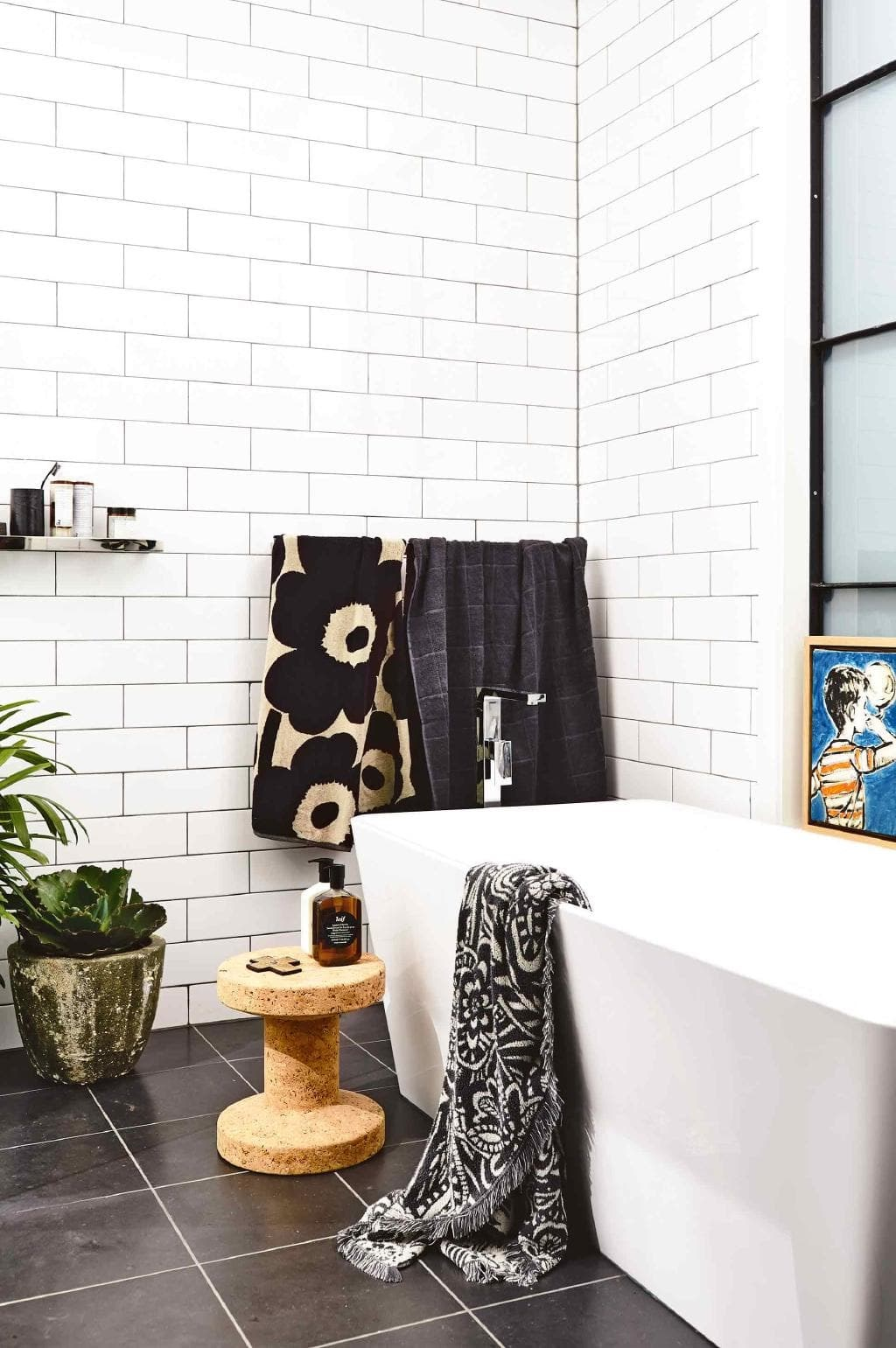 While a white bathroom will likely never go out of style, they can suffer from looking run-of-the-mill and clinical. Avoid this happening to you by accessorising with patterned towels and other textural objects like a cork stool or cement planter. *Photo: Derek Swalwell / Styling: Rachel Vigor*