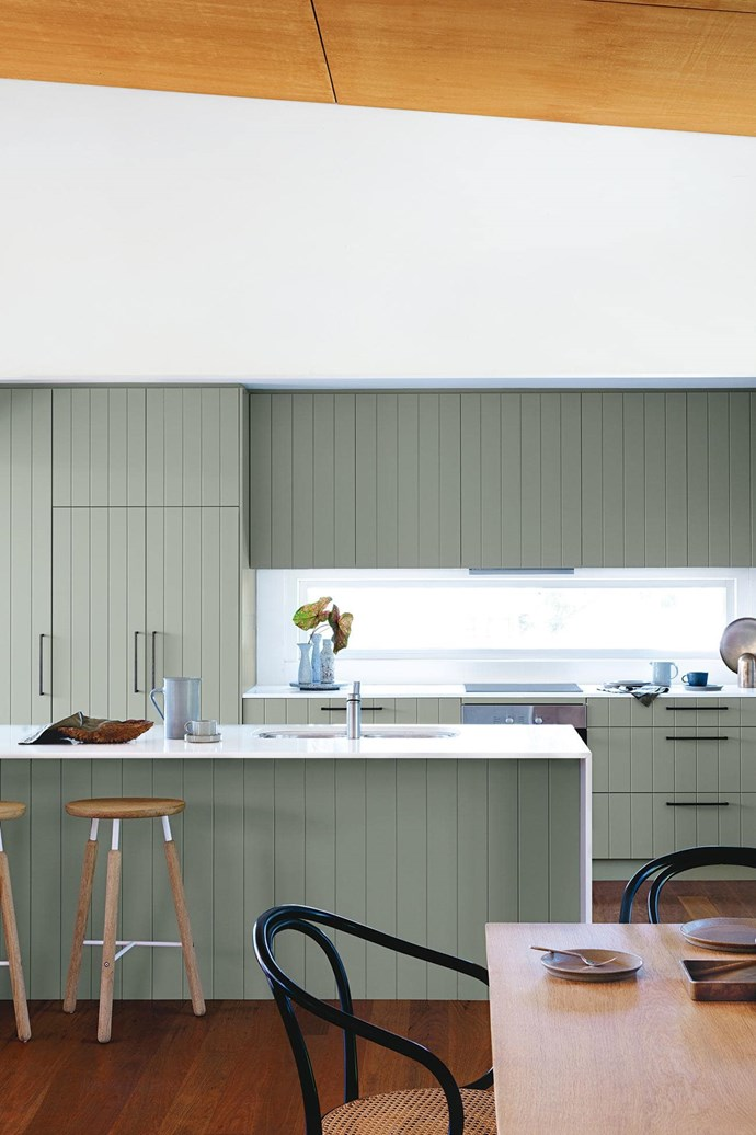 """**Natural attraction** Simple lines and a minimalist palette ensure this kitchen is in harmony with the impressive bushland vistas that surround it. Shiplap cabinetry in muted Dulux Tarzan Green hides an integrated fridge/freezer, minimising any shiny appliances in this peaceful zone, while a window splashback provides a connection to the natural environment. Above, a hoop-pine panelled ceiling adds warmth. _Design: [Arent & Pyke](http://arentpyke.com/