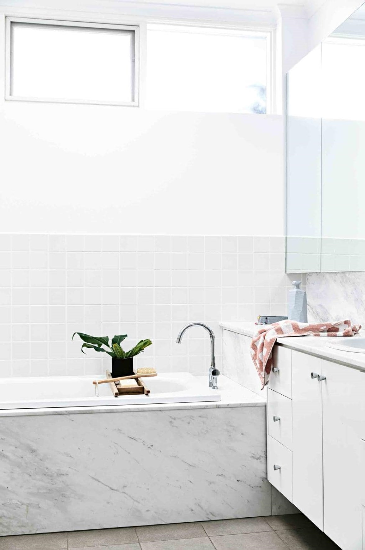 "A monochromatic colour palette and marble-clad inset tub gave this [small bathroom](https://www.homestolove.com.au/the-best-small-bathrooms-of-all-time-|target=""_blank"") an instant style update. *Photo: Derek Swalwell / Styling: Heather Nette King / Story: Inside Out*"