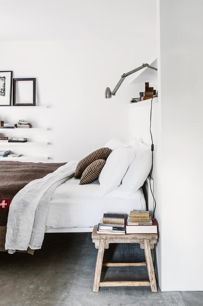 Built-in shelves provide handy storage space in the simple bedroom. Richly textured bedlinen and natural timber accents ensure this is a warm, welcoming space. Photographer: Stefania Giorgi