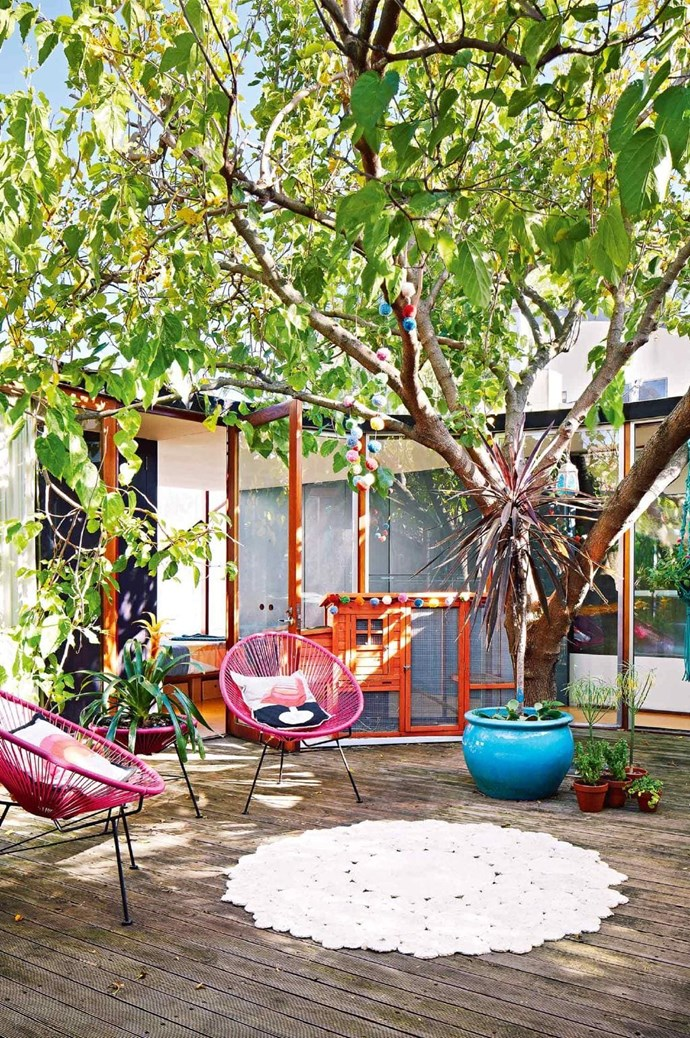 """Bright pops of colour and decorations give this [small outdoor area](https://www.homestolove.com.au/landscaping-ideas-for-small-backyards-3067 target=""""_blank"""") a joyful energy that appeals to kids and adults. *Photo:* Armelle Habib   *Styling:* Julia Green"""