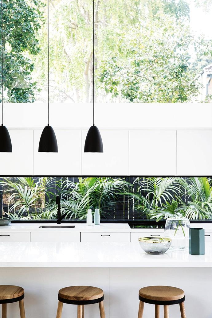 "A window splashback in this kitchen in a [minimalist home renovated on a budget](https://www.homestolove.com.au/a-small-budget-renovation-uses-smart-angles-to-perfect-the-minimalist-look-15011|target=""_blank"") is made all the more striking by the lush tropical garden beyond. *Photo: Chris Warnes*"