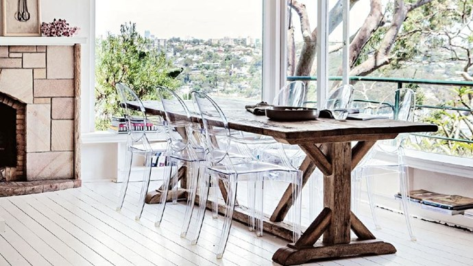 The clean lines of the Philippe Starck Ghost Chairs are perfect for this dining room with a view. The rustic table adds texture and helps to connect with the flora outside Photographer: Michael Wee