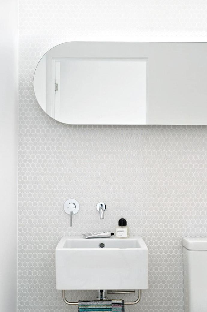 Mosaic tiles amplify the curved edged mirror and add a nice dose of interest and texture in this all-white bathroom Photographer: Justin Alexander